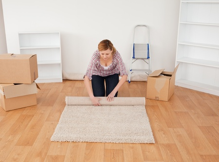 rolling up: Blonde woman rolling up a carpet to prepare to move house