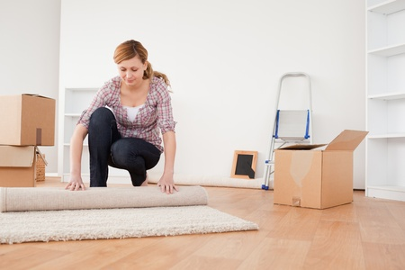rolling up: Lovely woman rolling up a carpet to prepare to move house  Stock Photo