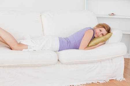 Smiling blonde woman resting while lying on the sofa in the living-room photo