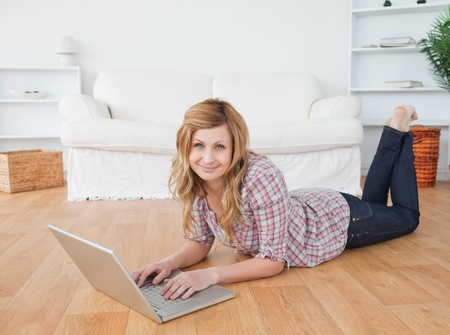 Cute woman looking at the camera while chatting on her laptop lying on the floor photo