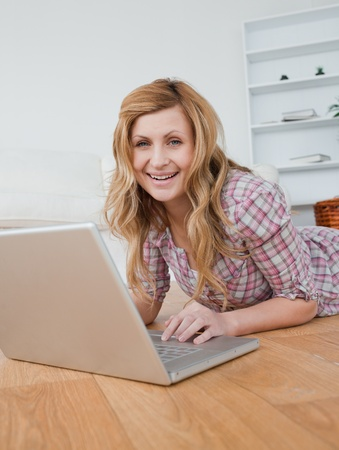 Blonde woman chatting on her laptop lying down on the floor photo