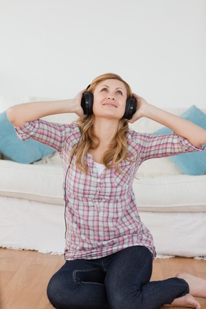 Happy blond-haired woman listening to music with headphones in the living-room Stock Photo - 10205830