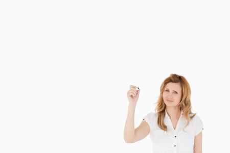 Cute woman drawing a scheme looking towards the camera on a white background photo