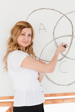 Teacher looking at the camera while drawing a scheme on a white board photo