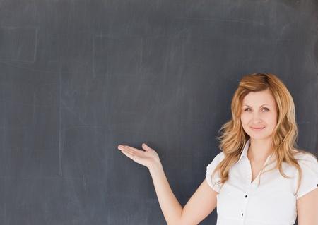 Cute female teacher showing an empty blackboard in a classroom photo