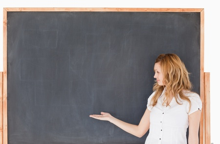 Cute female teacher showing an empty chalkboard in a classroom photo