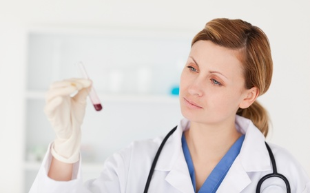 Female scientist looking at a red test tube in a lab photo