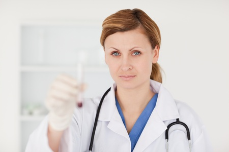 Blond-haired scientist looking at the camera while holding a red test tube in a lab Stock Photo - 10068812