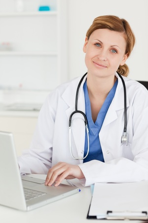 Young doctor looking at the camera while working in her surgery photo