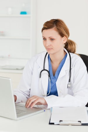 Concentrated doctor working on her laptop in her surgery photo