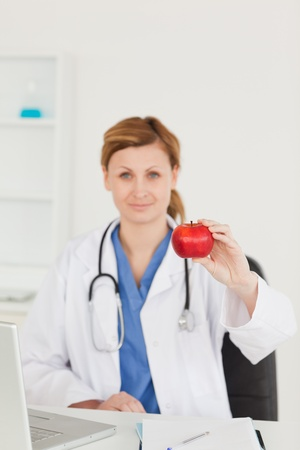 Cute female doctor showing a red apple to the camera in her surgery Stock Photo - 10068697