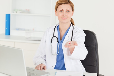Smiling female doctor showing pills to the camera while sitting in her office photo