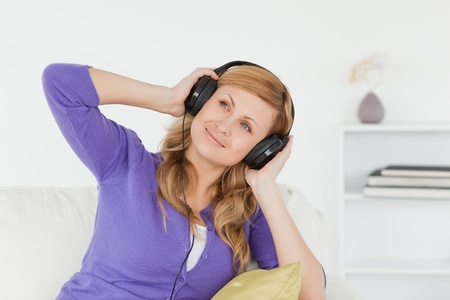 Attractive red-haired woman listening to music and enjoying the moment while sitting on a sofa in the living room photo