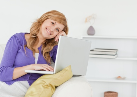 Smiling happy woman sitting on the sofa and using a laptop in her appartment Stock Photo - 10068810