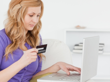 Concentrated woman sitting on a sofa is going to make a payment on the internet in her appartment Stock Photo - 10068682