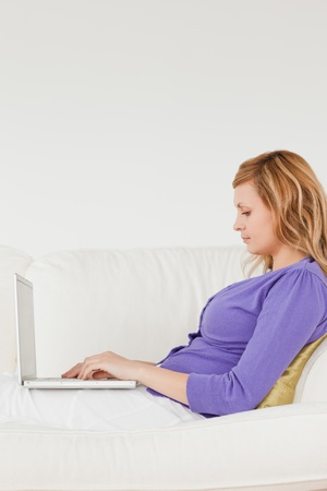 Good loooking red-haired woman using a laptop lying on a sofa in a studio photo