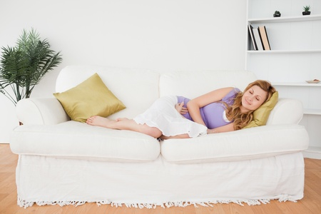 Attractive woman taking a rest while lying on a sofa in the living room photo