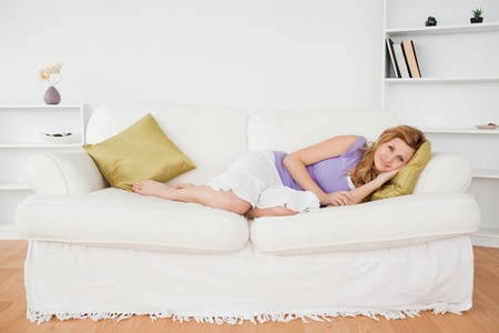 Attractive woman taking a rest and posing while lying on a sofa in the living room photo