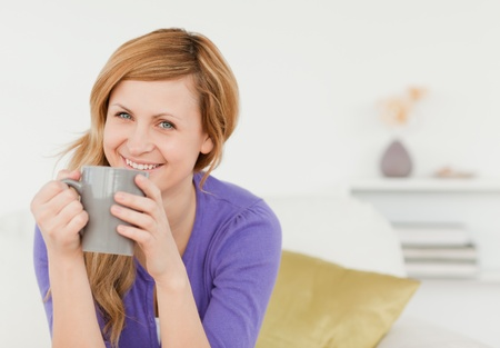 Smiling red-haired woman holding a cup of coffee and posing while sitting on a sofa in the living room photo