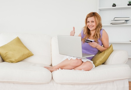 secured payment: Glad woman sitting on a sofa is going to make a payment on the internet while sitting on a sofa in the living room Stock Photo