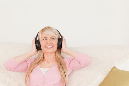 Beautiful woman listening to music on her headphones while sitting on a sofa in the living room photo