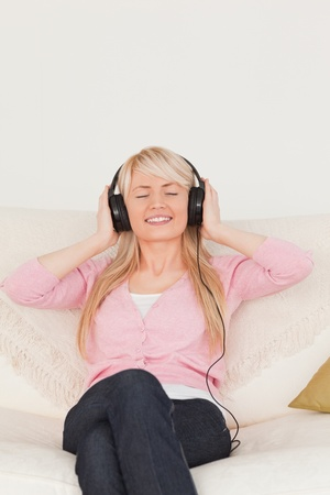 Beautifulfemale listening to music on her headphones while sitting on a sofa in the living room photo