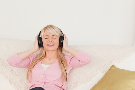 Good looking woman listening to music on her headphones while sitting on a sofa in the living room photo