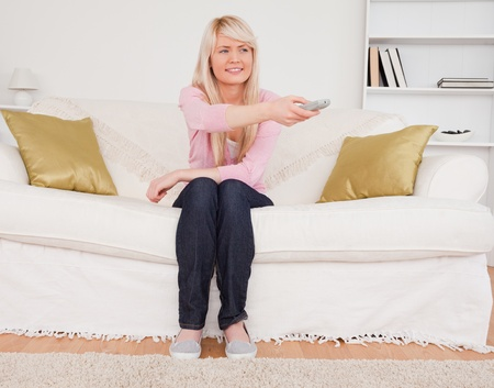 Good looking blonde female watching tv while sitting on a sofa in the living room photo
