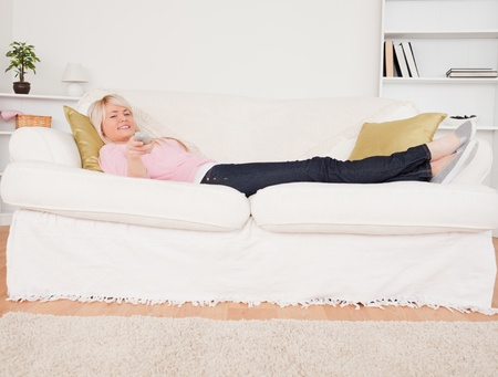 Pretty blonde female watching tv while lying on a sofa in the living room photo