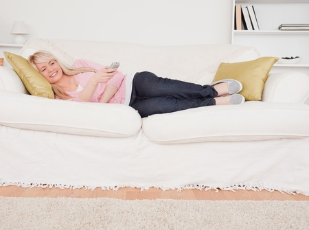 Attractive blonde female watching tv while lying on a sofa in the living room Stock Photo - 10196581