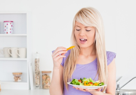 Happy female eating her salad in the kitchen photo