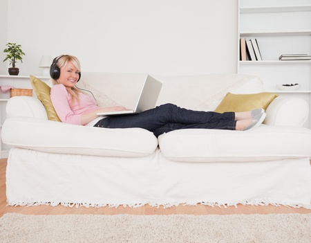Good looking woman listening to music on her headphones while lying on a sofa in the living room photo