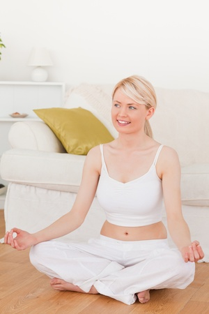 Young beautiful woman doing yoga in the living room in her appartement photo