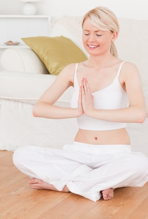 Young attractive woman doing yoga in the living room in her appartement photo