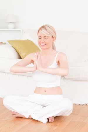 Young blonde woman doing yoga in the living room in her appartement photo