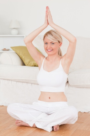Young good looking female doing yoga in the living room in her appartement Stock Photo - 10205822