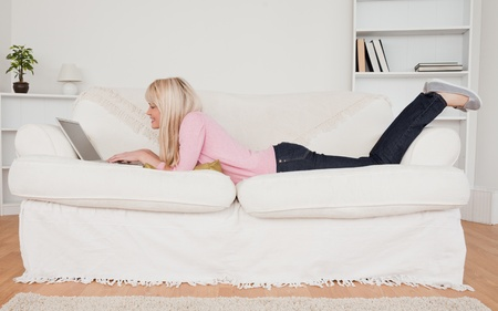 Young smiling woman relaxing with a laptop while lying on a sofa in her living room Stock Photo - 10196707