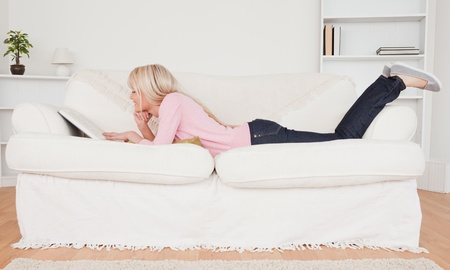 Young blonde woman relaxing with a book while lying on a sofa in her living room photo