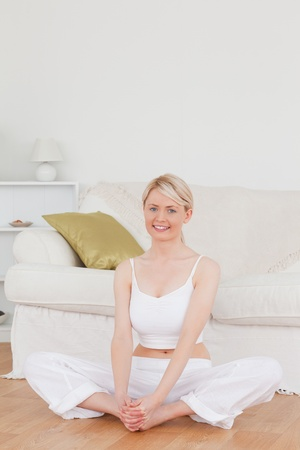 Young smiling woman doing relaxation exercises while sitting on the floor in the living room photo