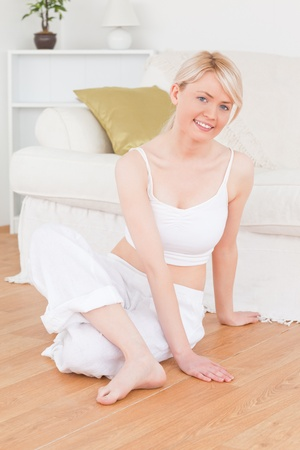 Young blonde woman doing relaxation exercises while sitting on the floor in the living room photo