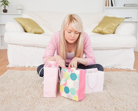 Blonde woman sitting in the living-room with her shopping bags photo