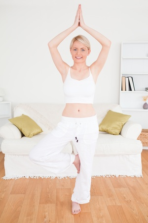 Young happy woman doing yoga in the living room in her appartment photo