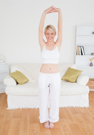 Beautiful blonde woman stretching in the living room in her appartment Stock Photo - 10205803