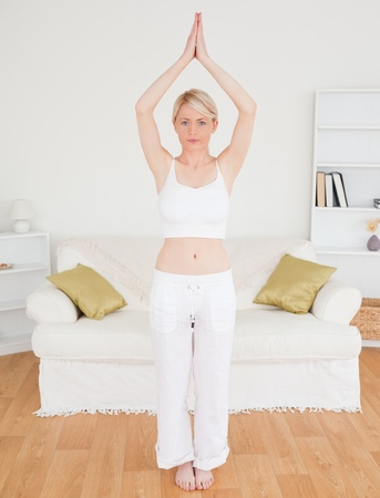 Attractive blonde woman stretching in the living room in her appartment Stock Photo - 10205744