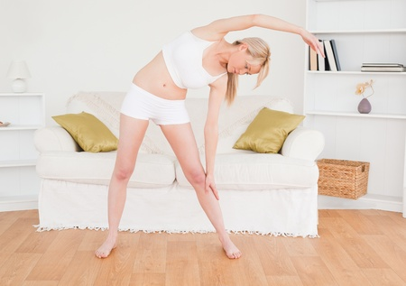 Gorgeous blonde female stretching in the living room in her appartment Stock Photo - 10196277