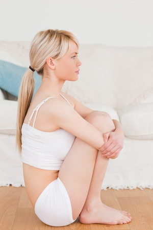 Beautiful blonde female in underwear posing while sitting on the floor in the living rom photo