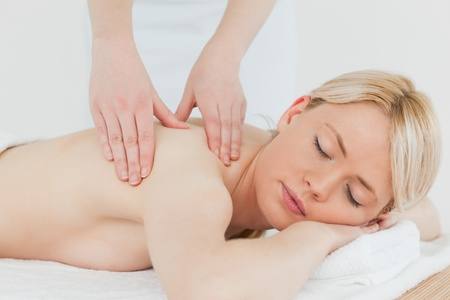 Closeup of young attractive blonde female receiving a back massage in a spa centre photo