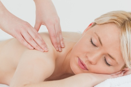 Closeup of young beautiful blonde woman receiving a back massage in a spa centre photo