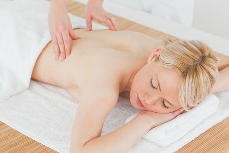 Closeup of young gorgeous blonde female receiving a back massage in a spa centre photo