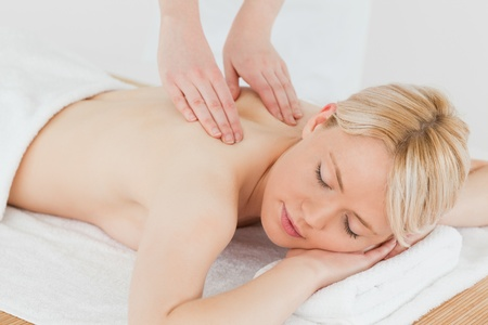 Closeup of young gorgeous blonde woman receiving a back massage in a spa centre photo